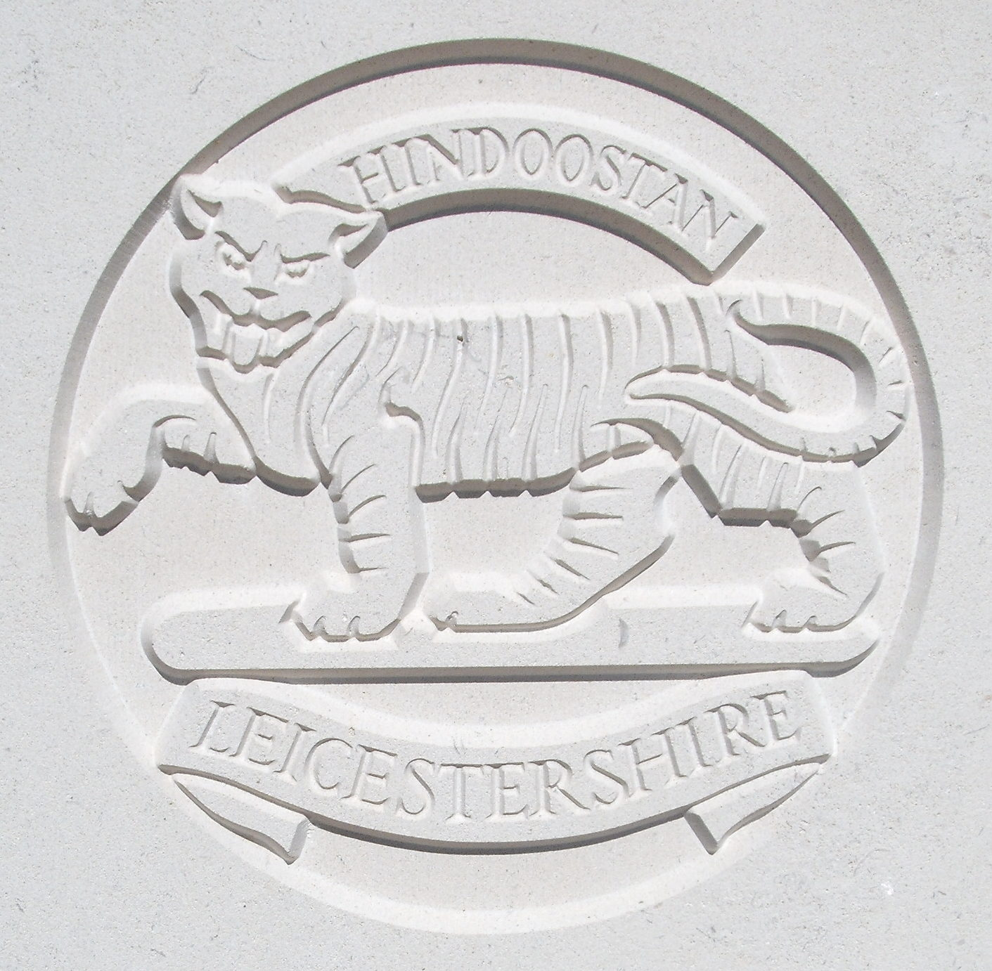 Capbadge of the Leicestershire Regiment on a CWGC headstone